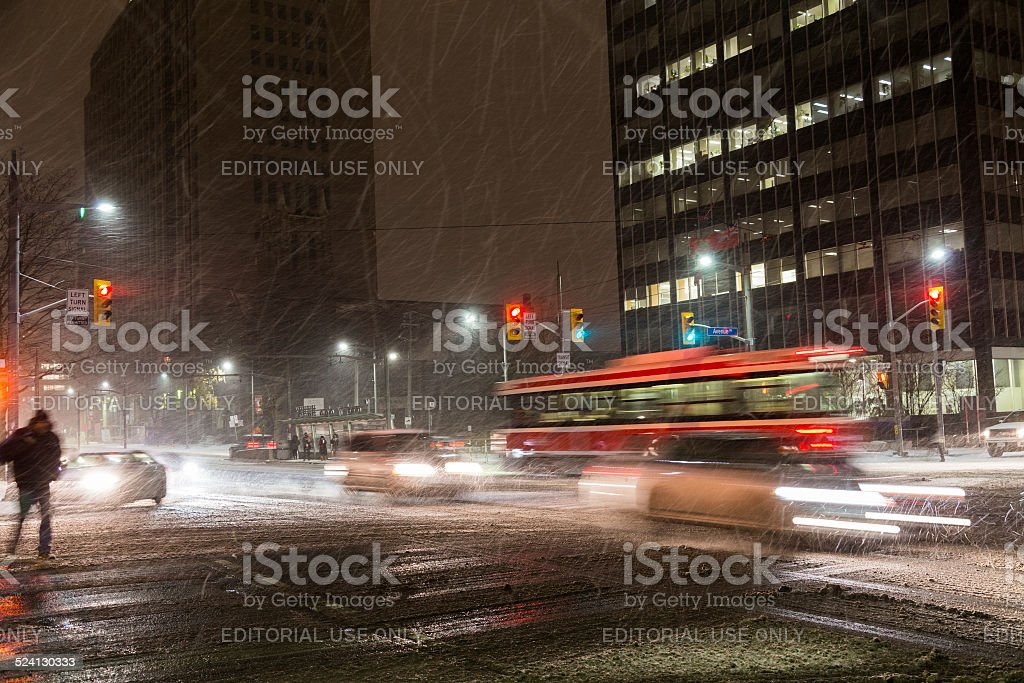 Snow Storm in Toronto Toronto, Canada - November 19, 2014: A snowstorm in Toronto at night, showing a Street Car and Traffic on the road Arranging Stock Photo