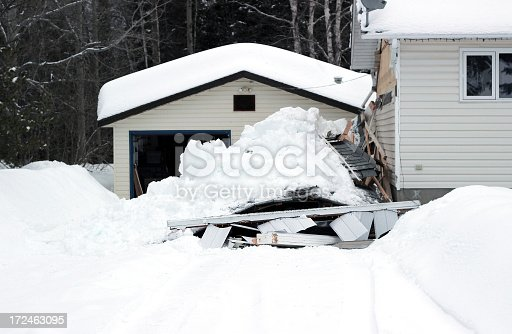 A photograph of a snow covered carport that has collapsed on top of two vehicles.