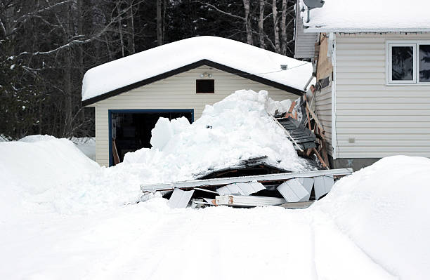 Snow that has collapsed a roof A photograph of a snow covered carport that has collapsed on top of two vehicles. collapsing stock pictures, royalty-free photos & images