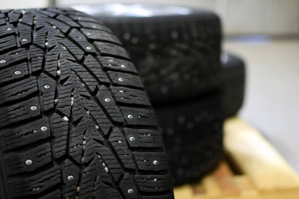 Snow tires with metal studs in garage. Small stones in the groove. Snow tires with metal studs in garage. Small stones in the groove. Close up image, shallow depth of field. studded stock pictures, royalty-free photos & images