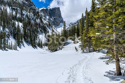 A snow hiking trail winding along side of froze Dream Lake towards towering Hallett Peak. Rocky Mountain National Park, Colorado, USA.