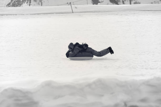 Snow tubing on ski resort at sunny winter day in mountains - foto stock