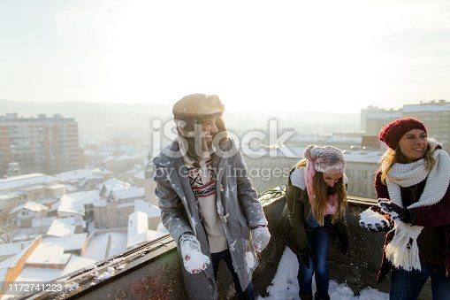 Group of friends is enjoying sunny winter afternoon and having a fun snowball fight on a rooftop terrace that overlooks the city