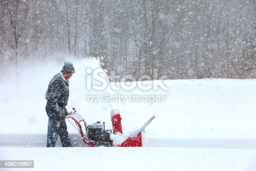 A man using a snowblower in a snowstorm.