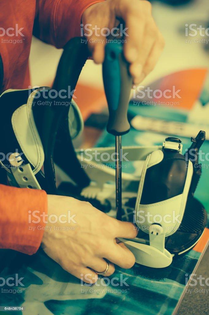 Snowboard repair shop worker adjust the bindings stock photo