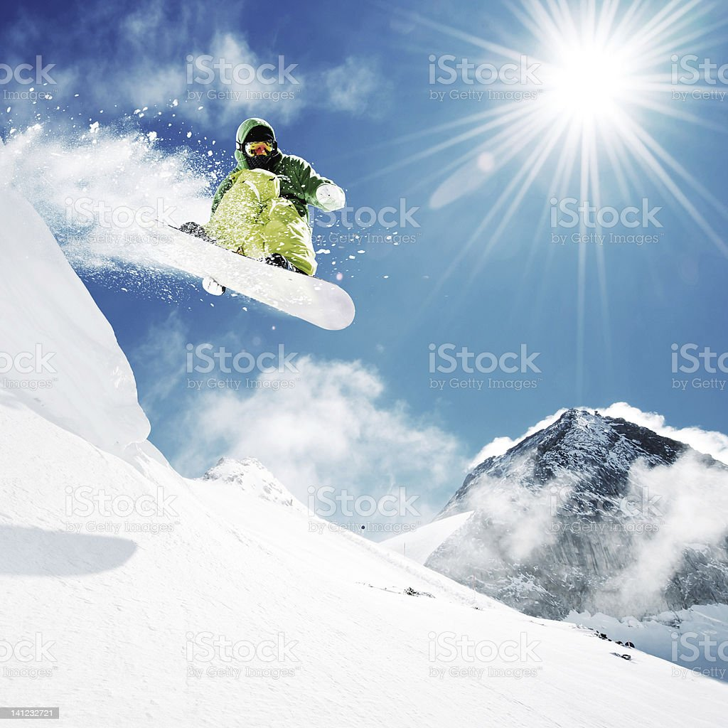 Snowboarder at jump in high mountains at sunny day.