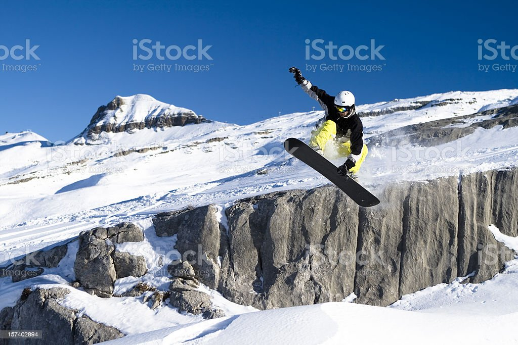 Snowboarder catching air as he clears the drop off stock photo