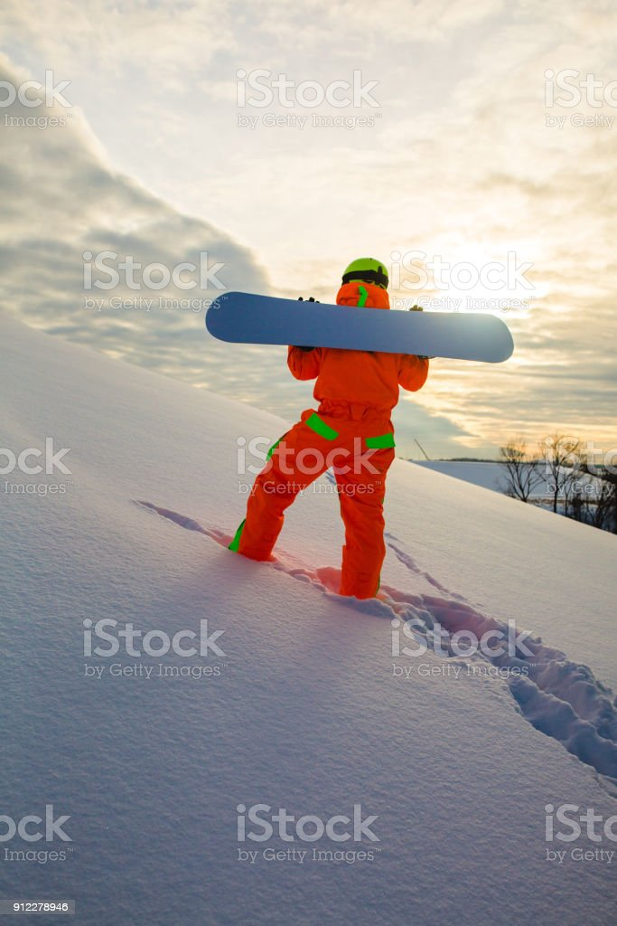 Snowboarder climbing on the top of ski slope stock photo