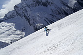 Snowboarder descends on off-piste ski slope in high snowy mountains at sunny winter day. Caucasus Mountains, region Dombay. View from above.