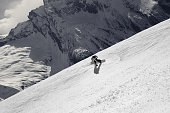 Snowboarder descends on off-piste ski slope in high snowy mountains at sunny winter day. Caucasus Mountains, region Dombay. View from above. Black and white retro toned landscape.