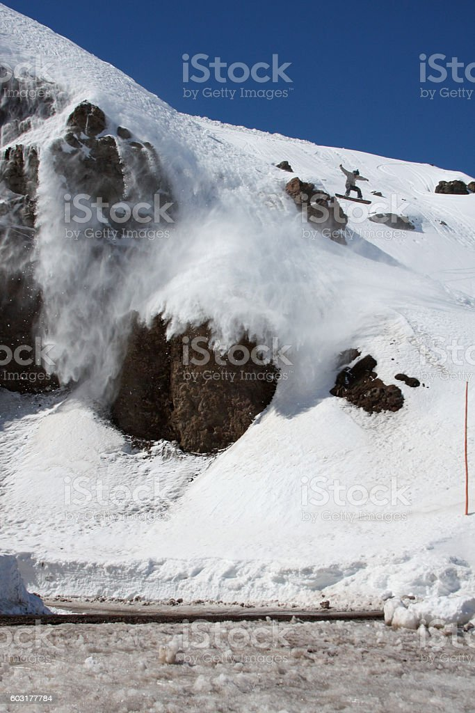 Snowboarder Does Big Air Jump off Steep Rock Cliffs stock photo