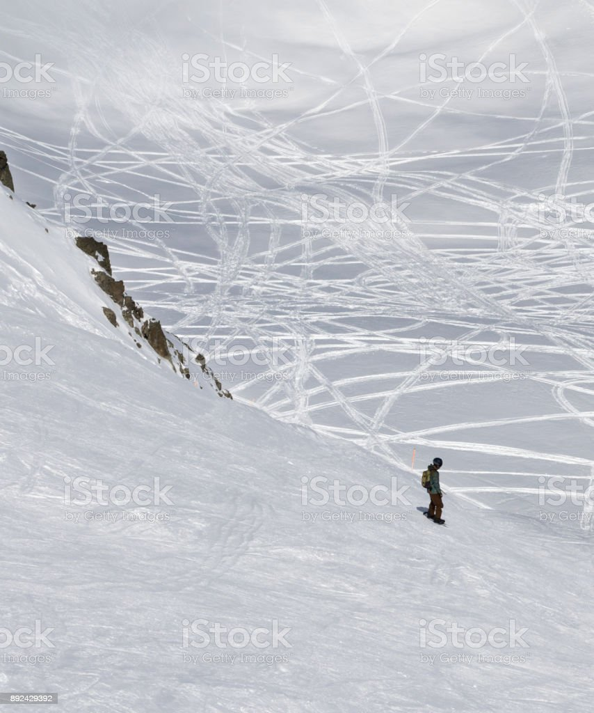 Snowboarder downhill on freeriding slope at sun cold day stock photo