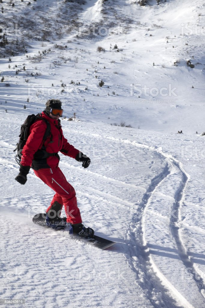 Snowboarder downhill on snow off piste slope in sun winter morning stock photo