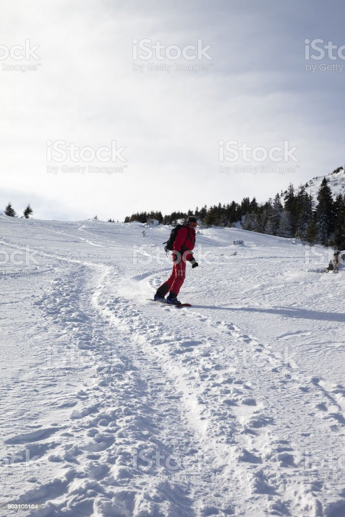 Snowboarder downhill on snow off-piste slope in winter morning stock photo