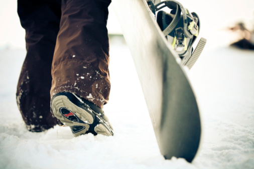Snowboarder dragging the snowboard over the snow