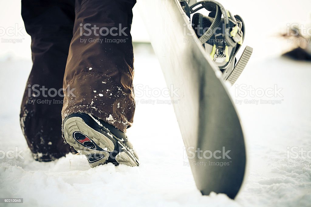 Snowboarder dragging the snowboard over the snow stock photo