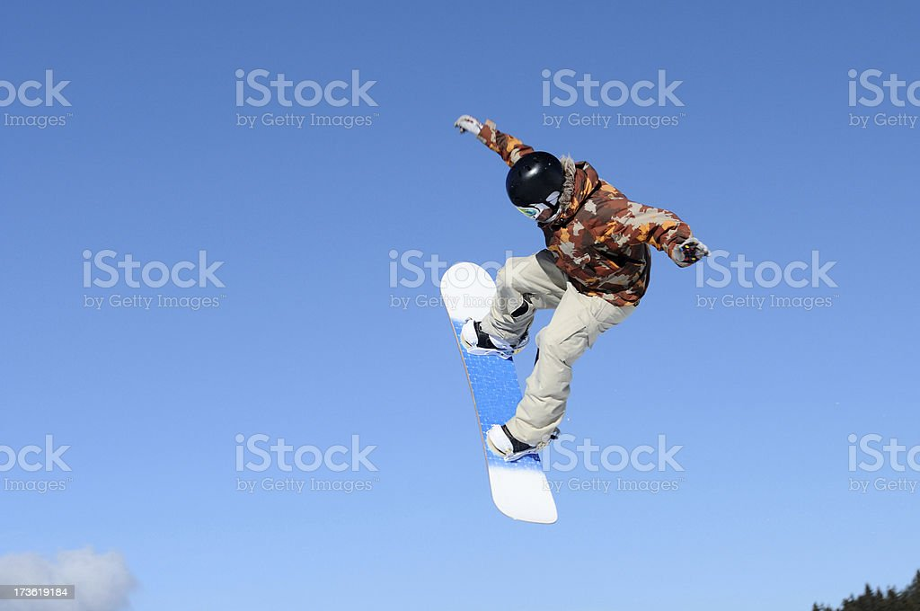 Snowboarder flying against the blue sky royalty-free stock photo