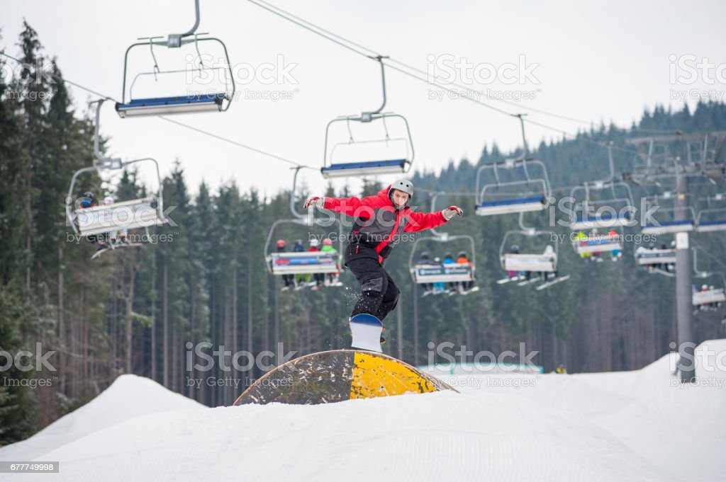 Snowboarder flying over a hurdle in winter day royalty-free stock photo