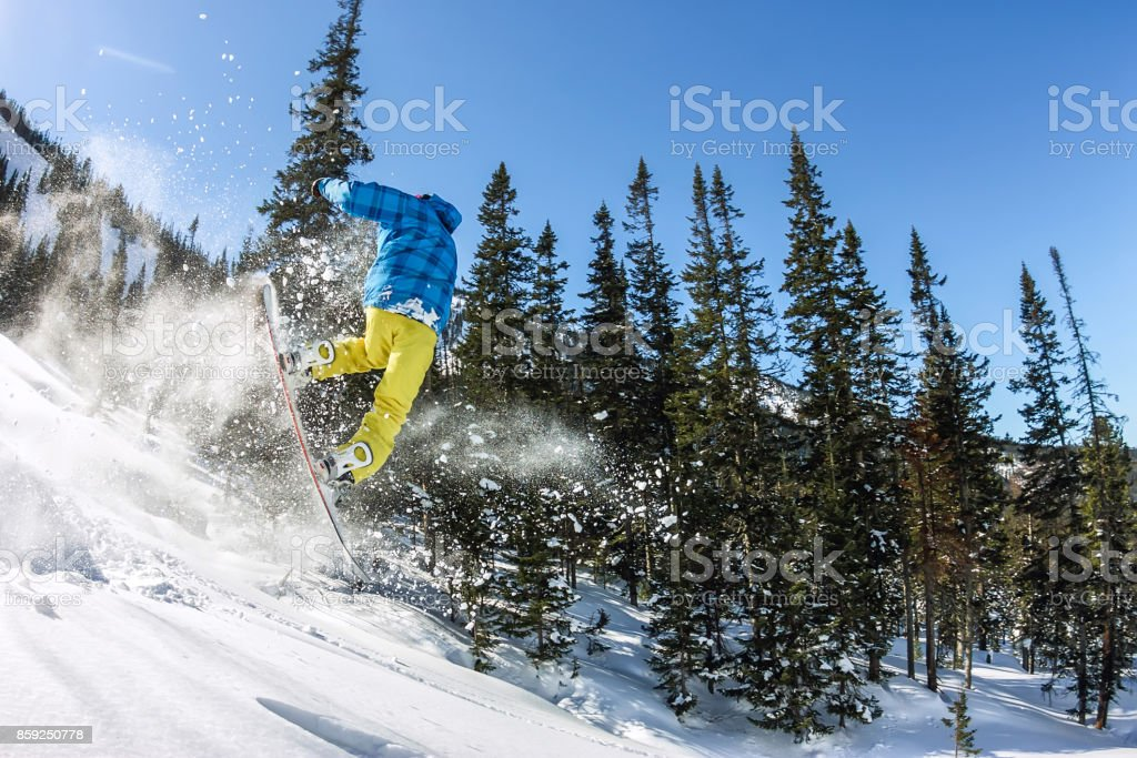 Snowboarder freerider jumping from a snow ramp in the sun on a background of forest and mountains stock photo
