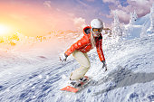 Snowboarder in orange hoodie and white pants glides on an orange snowboard over the fresh snow in a wintry mountain landscape