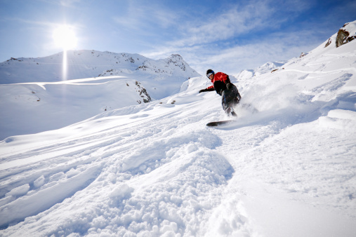 A snowboarder going downhill in the snow in the Alps