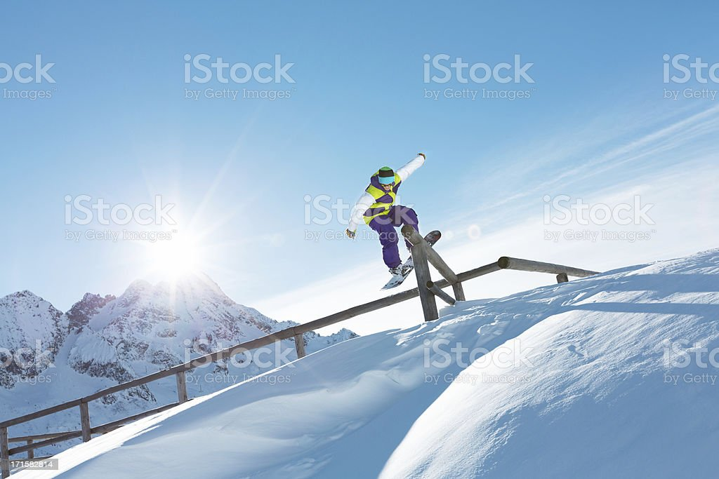 Snowboarder grinding stock photo