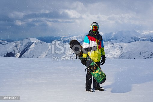 istock Snowboarder holding snowboard in hand standing in the snowfall 956449922