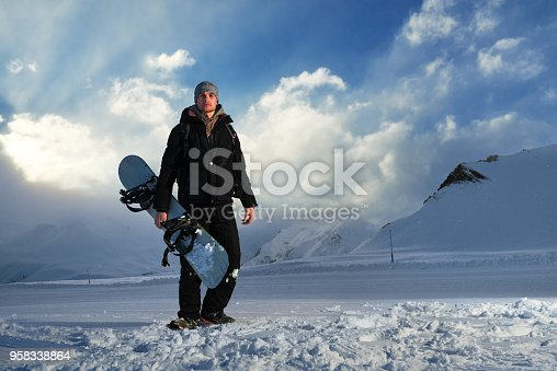 istock snowboarder in black suit standing on the road 958338864