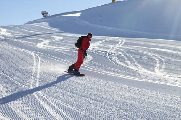 Snowboarder in red downhill on snowy ski slope - foto stock