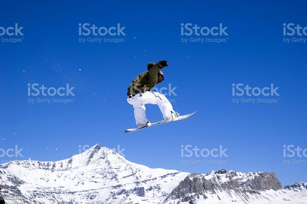 Snowboarder in the air with mountains in the background royalty-free stock photo
