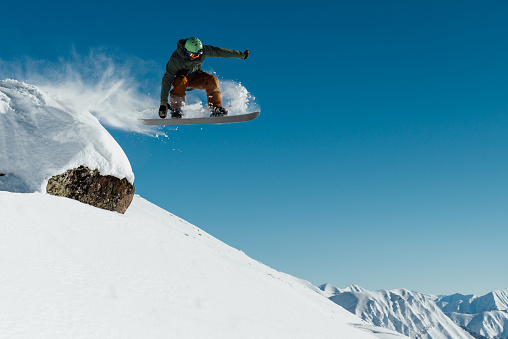 snowboarder in the outfit drops off the ledge of the stone onto the fresh snow creating a spray of snow