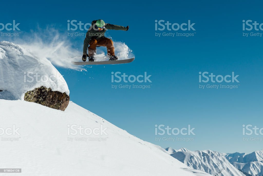 snowboarder in the outfit drops off the ledge of the stone onto the fresh snow creating a spray of snow stock photo