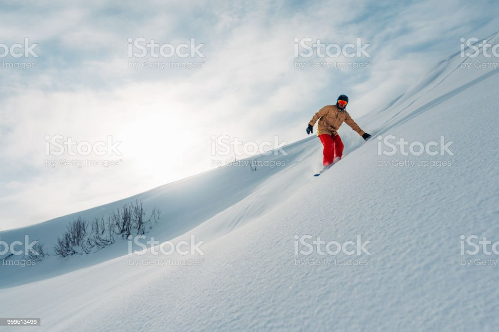 snowboarder is riding from snow hill stock photo