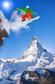 Snowboarder jumping against Matterhorn peak in Switzerland