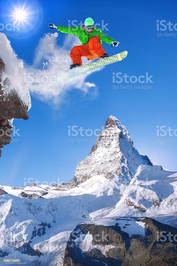 Snowboarder jumping against Matterhorn peak in Switzerland stock photo