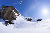 Snowboarder jumping off a cliff.