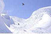 Snowboarder jumping and spinning over a gap.