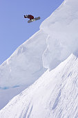 Snowboarder jumping off a cornice.