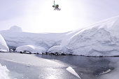 Snowboarder jumping and spinning over a frozen river.