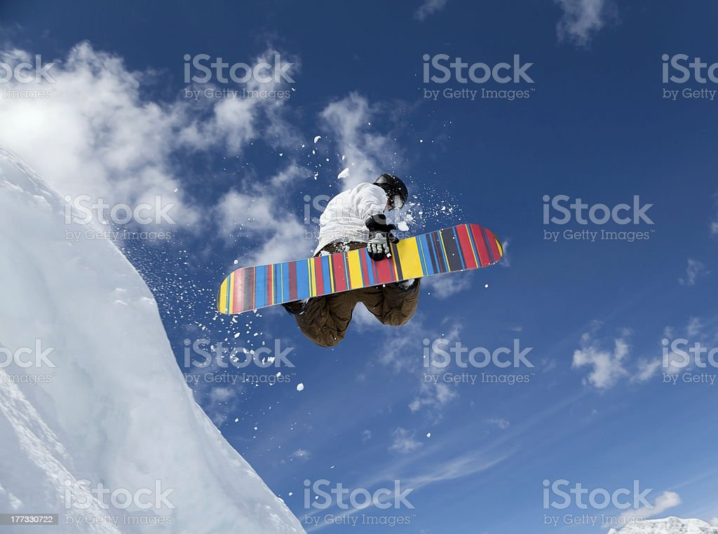 Snowboarder jumping while holding board stock photo