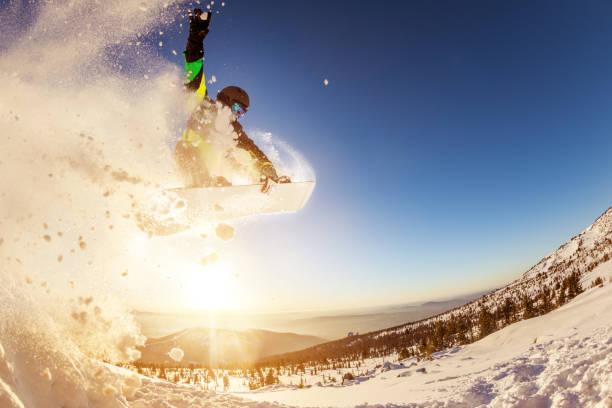 Snowboarder jumps against sunset sun