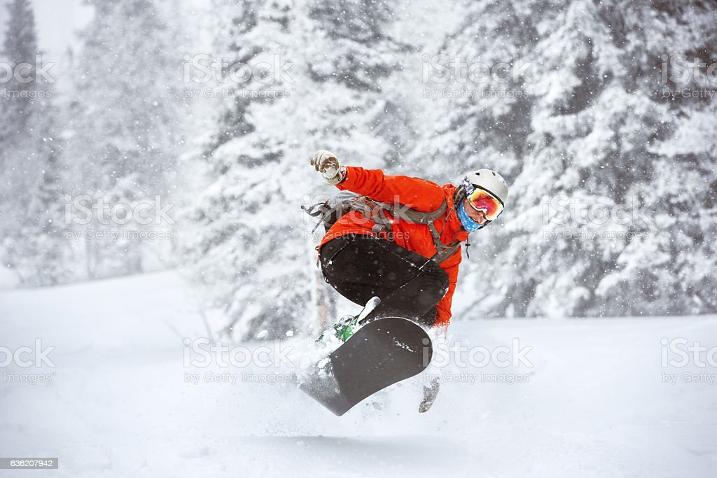 Snowboarder jumps backcountry freeride off-piste ski resort stock photo
