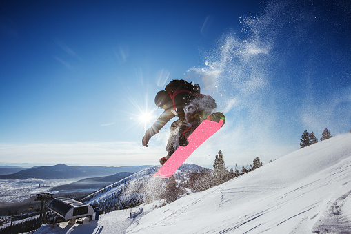 Snowboarder jumps on blue sky backdrop in mountains trick