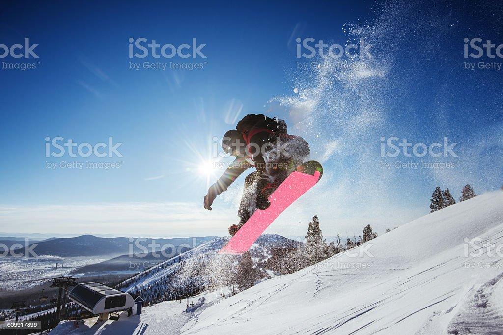 Snowboarder jumps on blue sky backdrop in mountains trick - foto de stock