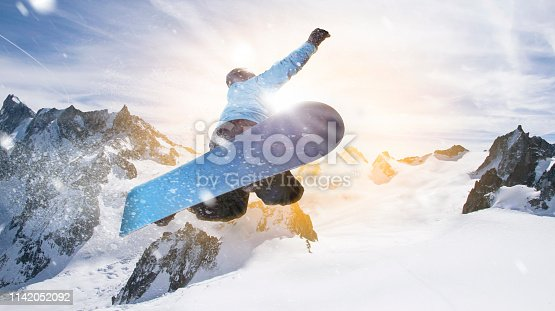 man on a snowboard jumps through the air next to sunlight. he wears blue snowboard clothing and enjoys the fun.
