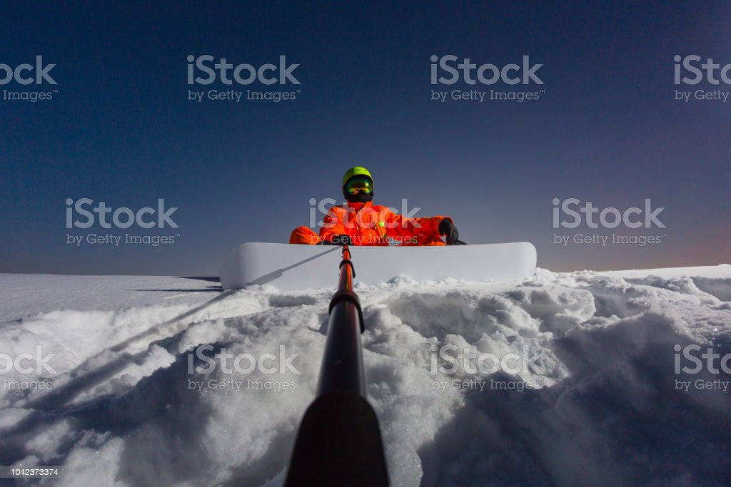 Snowboarder making a selfie by his action camera on the top of the ski slope stock photo