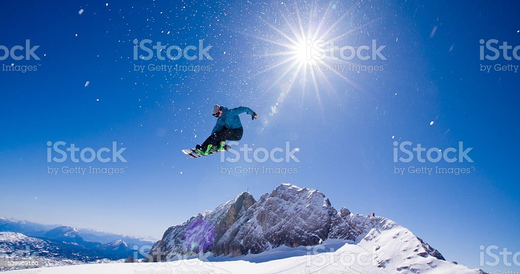 Snowboarder making stunt in the air stock photo