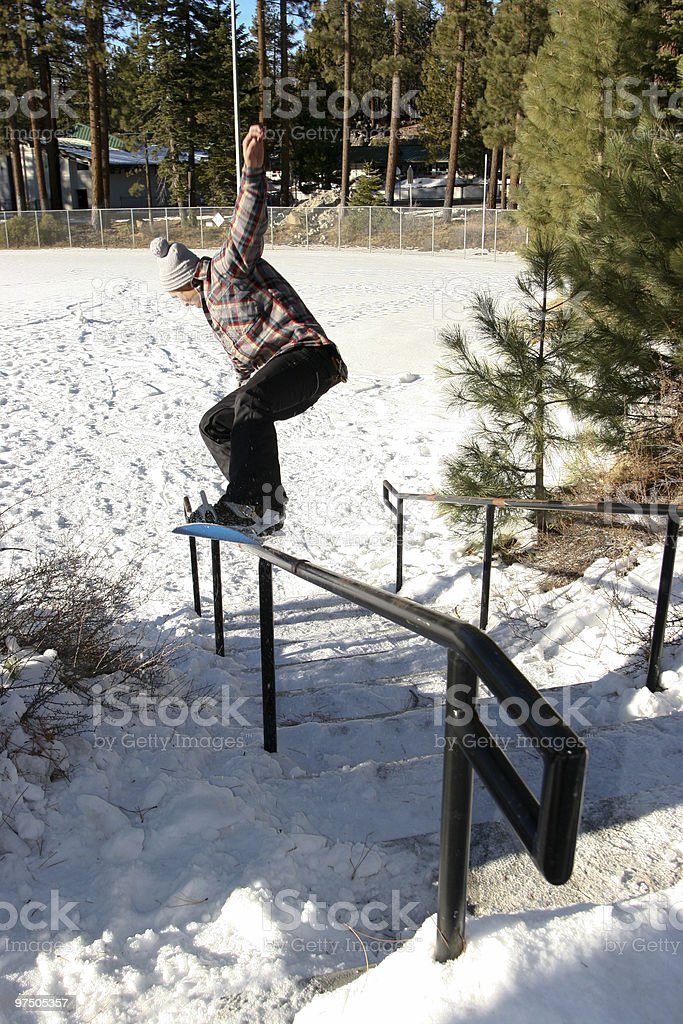 Snowboarder nosegrind on handrail royalty-free stock photo