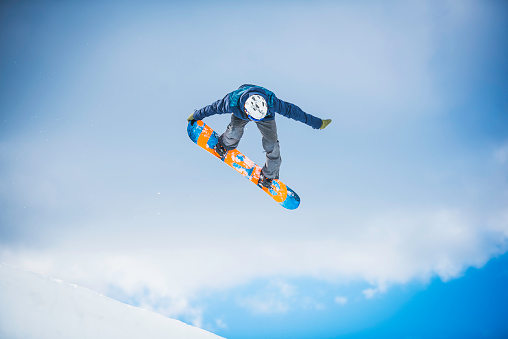 Snowboarder performing a tail grab