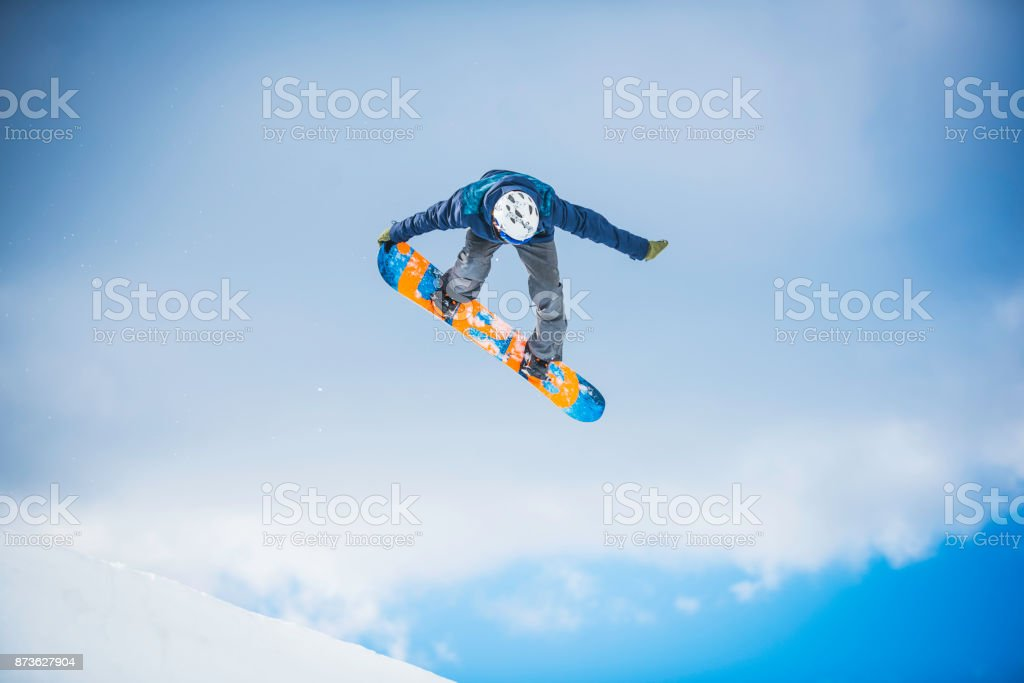Snowboarder performing a tail grab stock photo